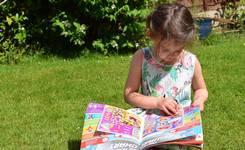 Kind dat tijdschrift leest in tuin
